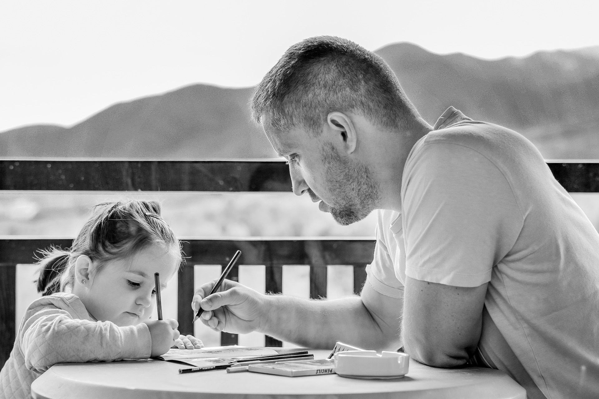 Father and daughter colouring together