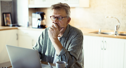 Middle-aged white man looking concerned in front of his laptop