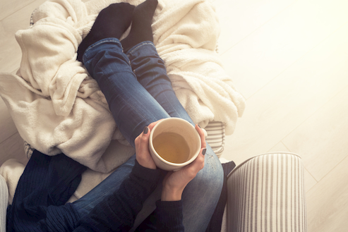 A woman's legs in jeans, holding a cup of black coffee