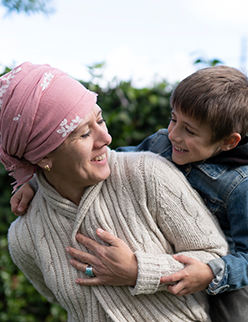 Woman in pink headscarf smiling with son