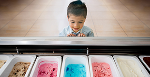 A young boy happily looking at seven different flavours of ice-cream through a protective screen