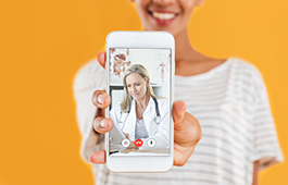 Young woman holding a phone to the screen on which there's a GP on a video call.