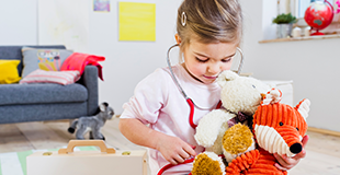 Young girl holding a stethoscope to her toys 310x160
