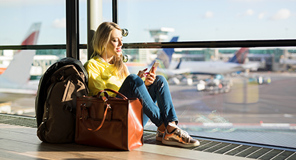 Young woman waiting at the airport whilst using her phone 425x230