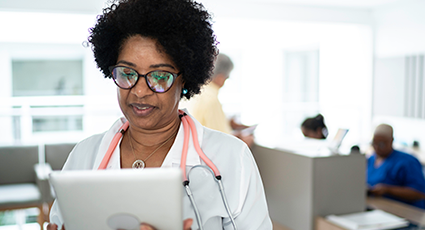 Black female doctor wearing stethoscope looking at a tablet device
