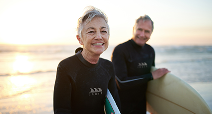 Man and woman holding surf boards by the sea