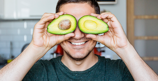 Man holding avocado halves up to his eyes