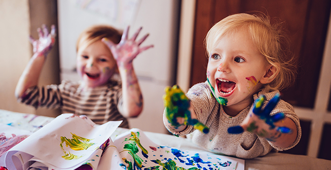 Two children painting with their hands