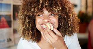 Young woman with mouthful, eating a sandwich and laughing