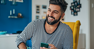 Man with beard and striped top holding his mobile whilst laughing