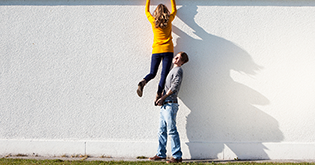 Man lifting woman over a wall