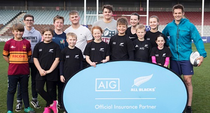 Photo of 13 children from Winston's Wish and Richie McCaw with standing behind an AIG and All Blacks Insurance Partner foldout poster.