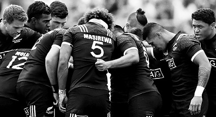 11 male All Blacks players in a team talk huddle.